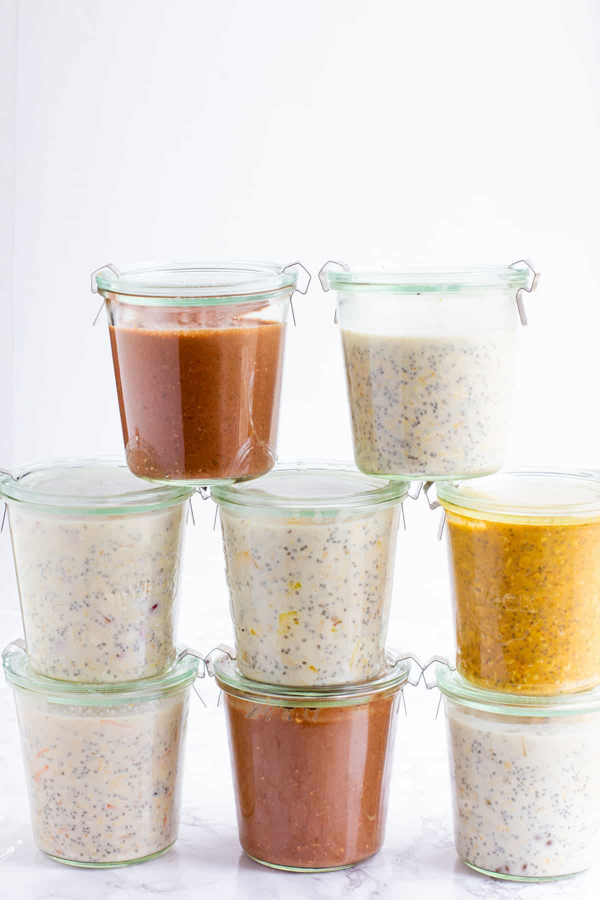 8 glass jars filled with different flavors of overnight oats stacked in a pyramid.