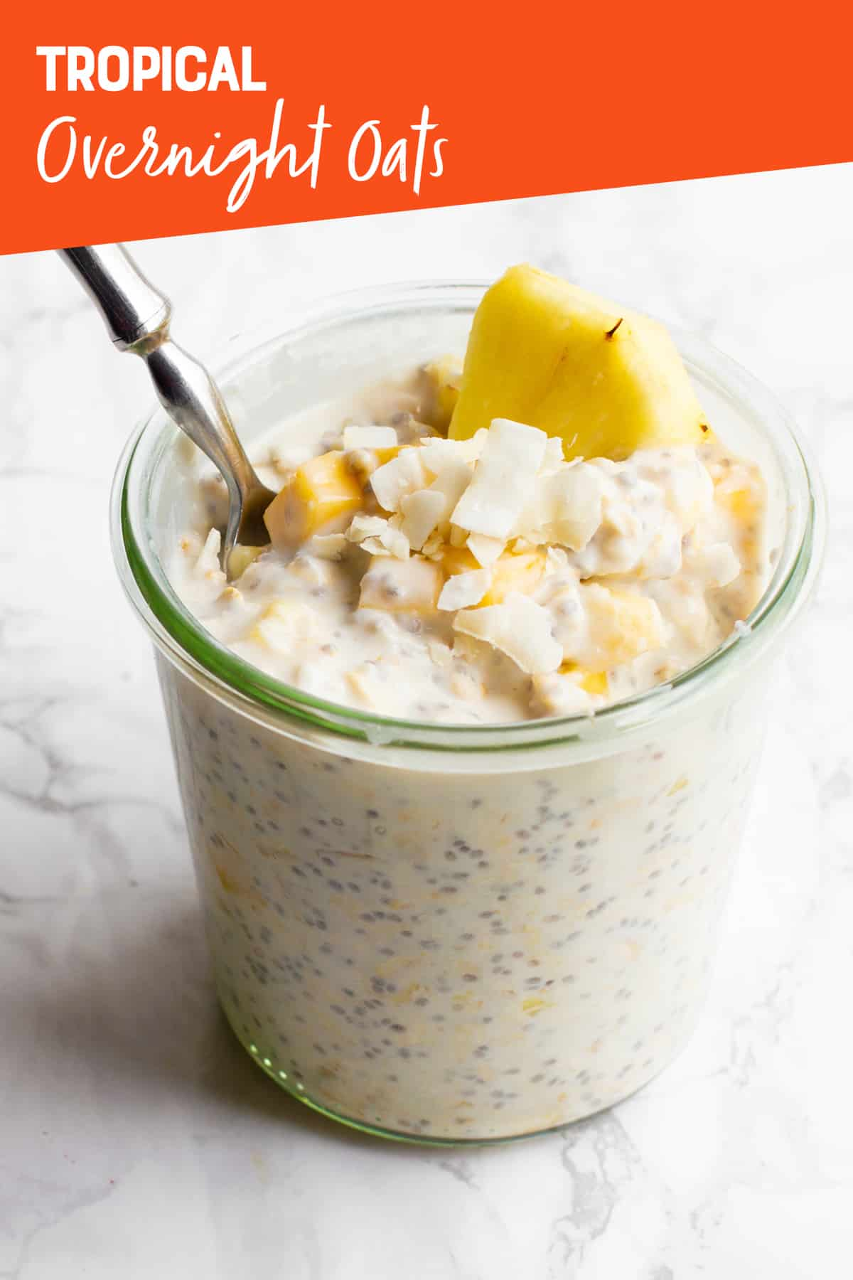 """A clear glass jar filled with Tropical Fruit Overnight Oats, with a spoon sticking out. A text overlay reads """"Tropical Overnight Oats."""""""