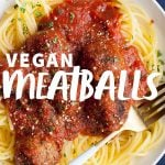"White plate filled with spaghetti, vegan meatballs, and marinara sauce on a blue background. A text overlay reads ""Vegan Meatballs."""