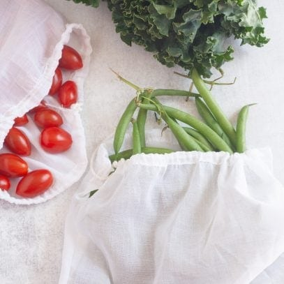 Three white cotton voile reusable produce bags filled with kale, cherry tomatoes, and green beans.