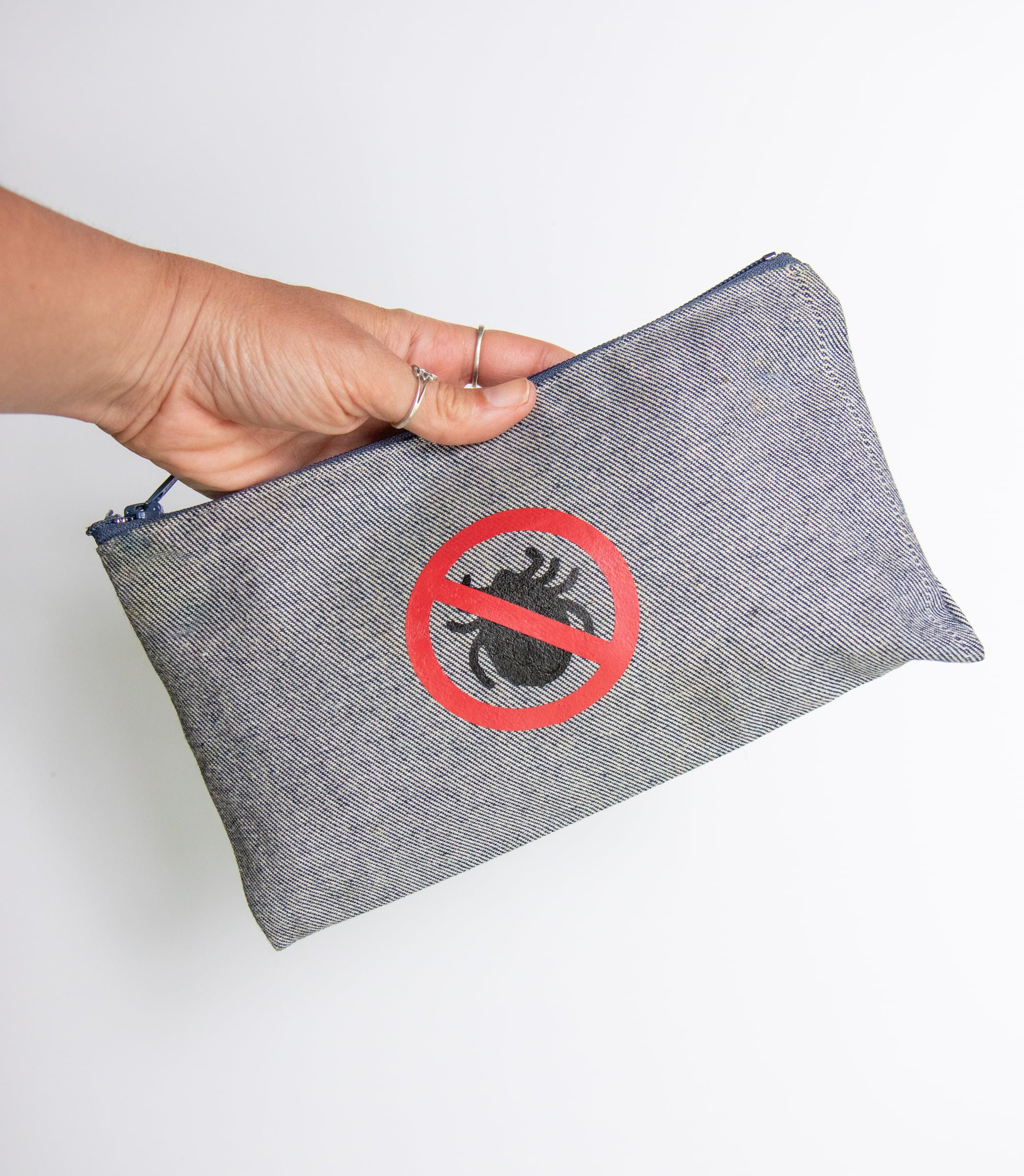 """Hand holding a gray pouch with a """"no ticks"""" label. The pouch contains a tick kit - everything you need to deal with a tick bite."""