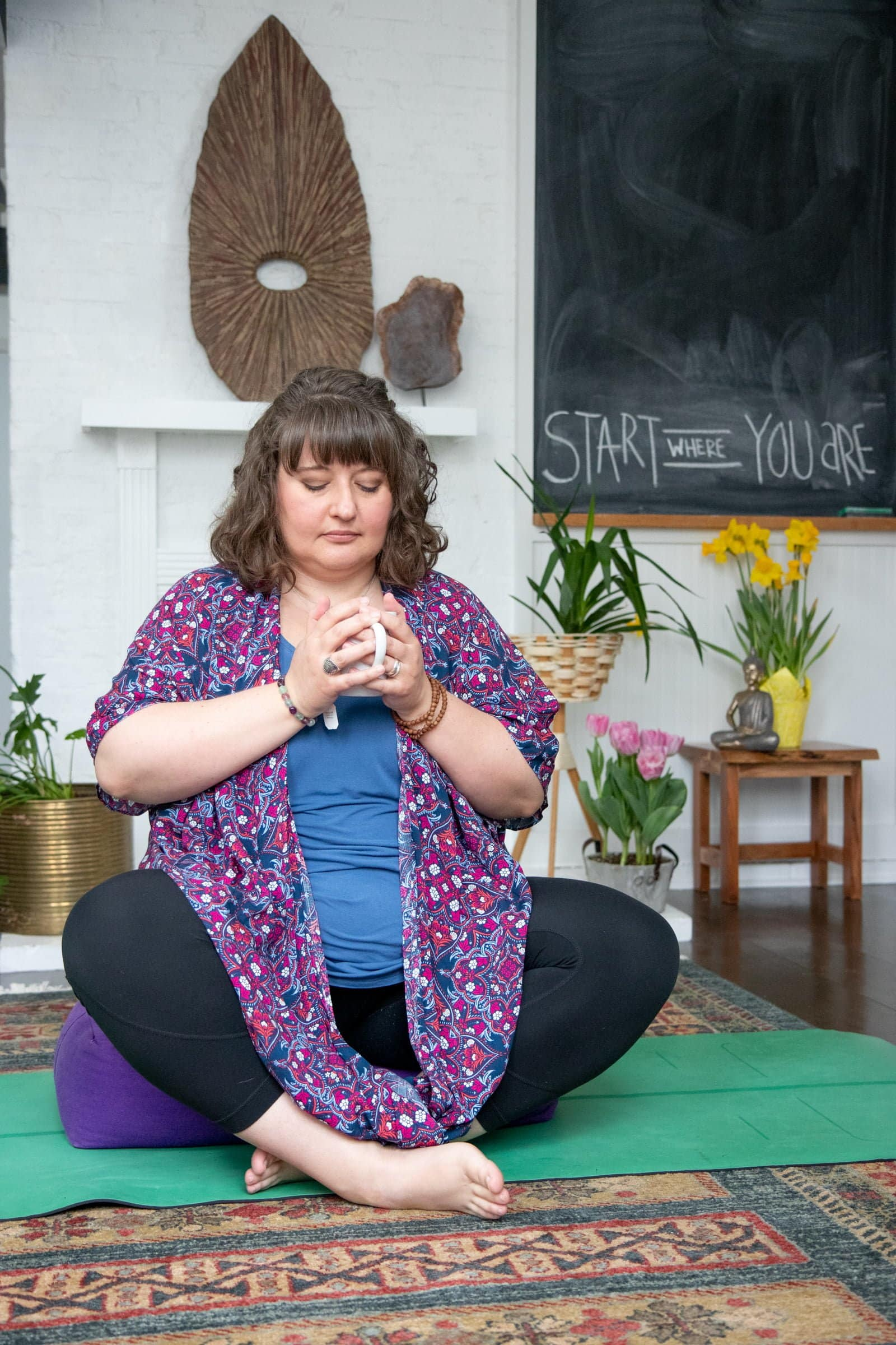 Brunette woman sitting cross-legged on a yoga mat with her eyes closed. She holds a mug of tea as she starts meditating.