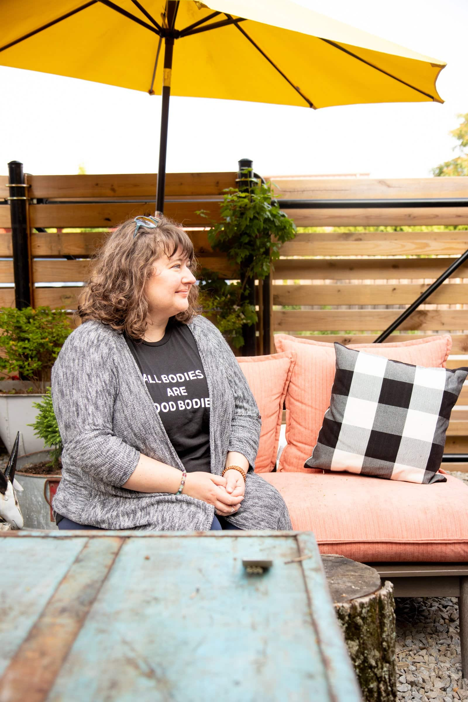 Brunette curly-haired woman sitting pensively on an outdoor couch.