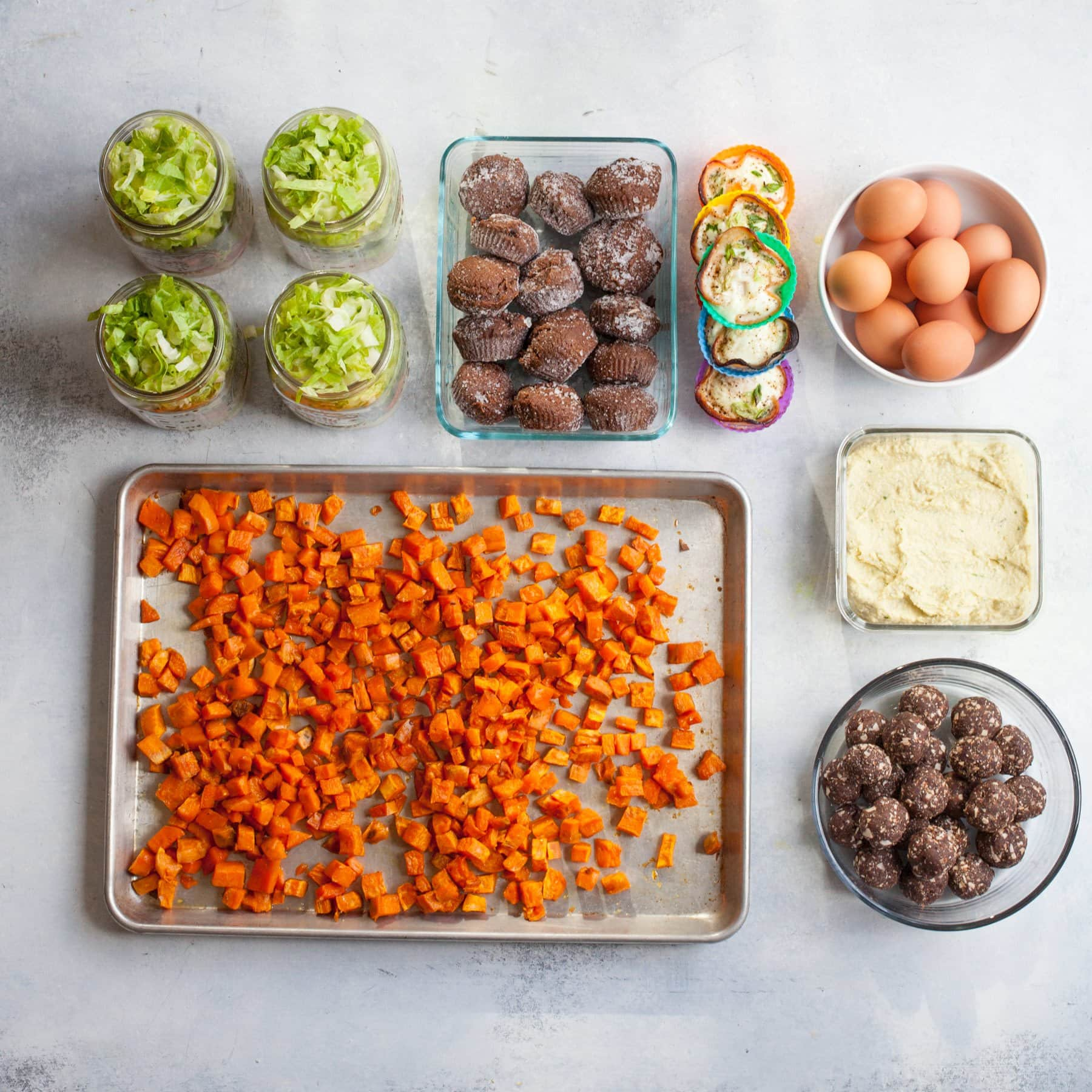 Meal prep components laid out in individual containers - roasted sweet potato cubes, salads in jars, muffins, egg cups, hard boiled eggs, hummus, and date bites.