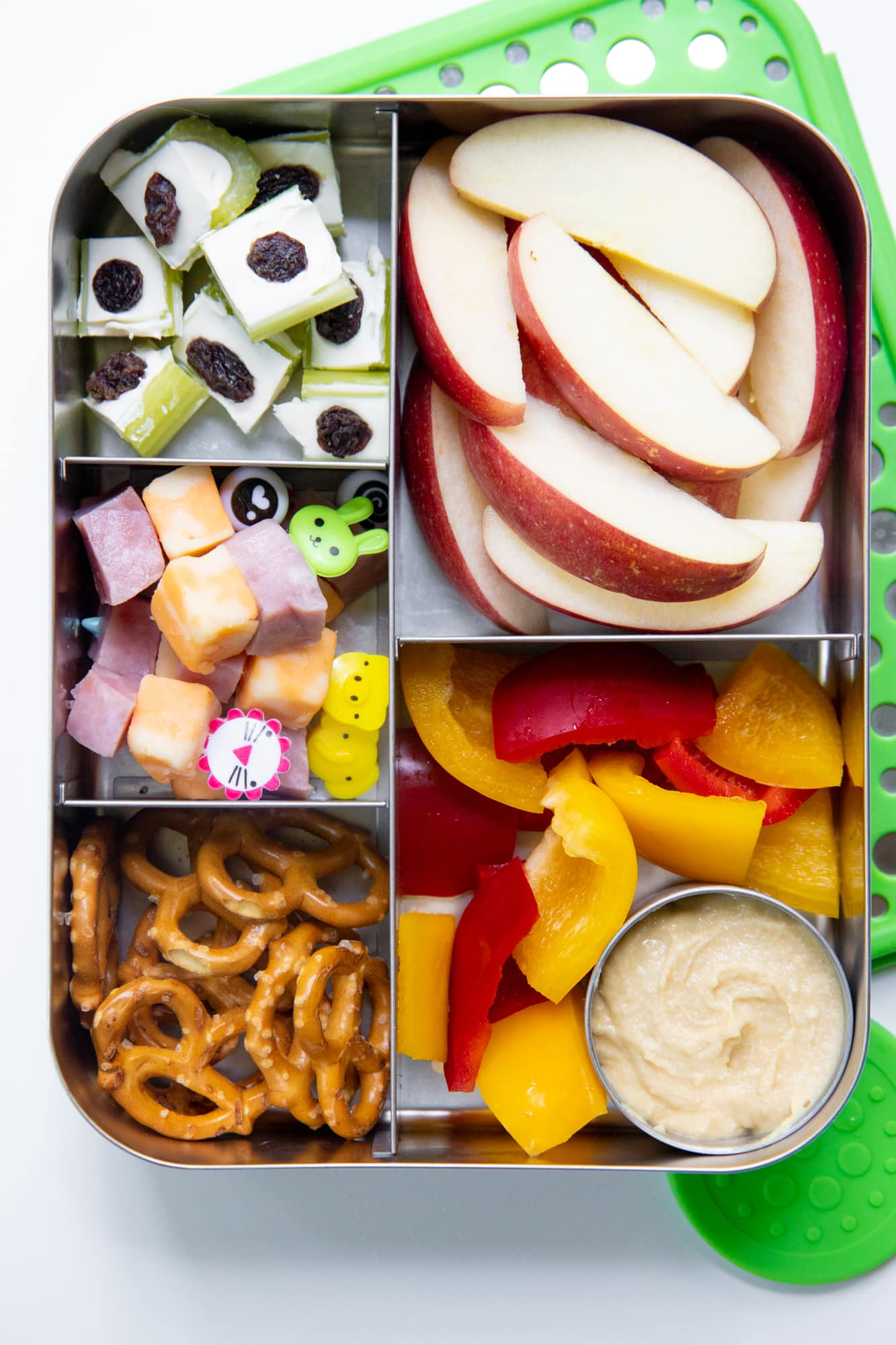 Close-up of a bento-style stainless steel lunch box filled with apple slices, pretzels, ham and cheese on toothpicks, bell peppers and hummus, and stuffed celery.