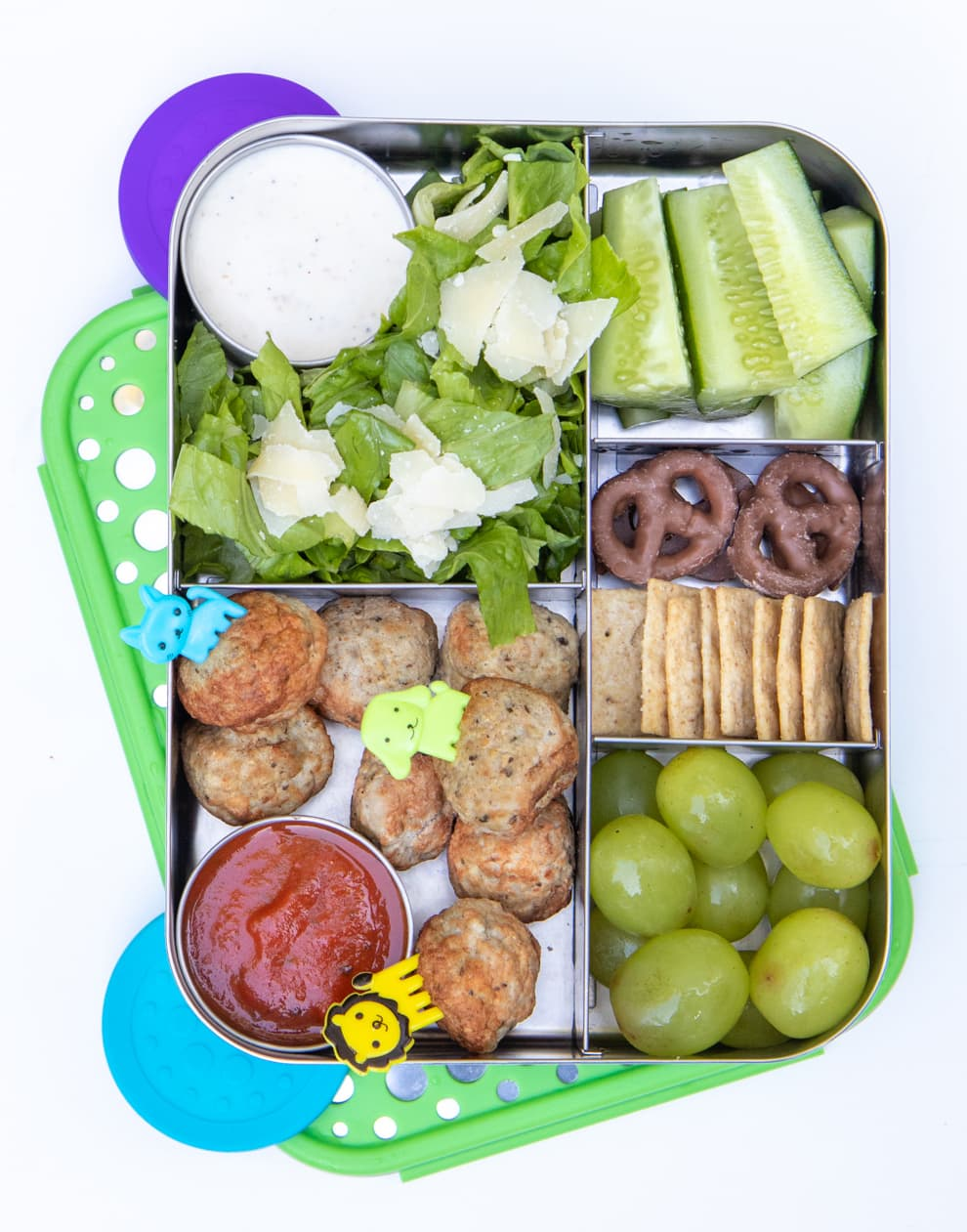 Stainless steel divided lunch box filled with meatballs, grapes, celery, pretzels, salad, and crackers.
