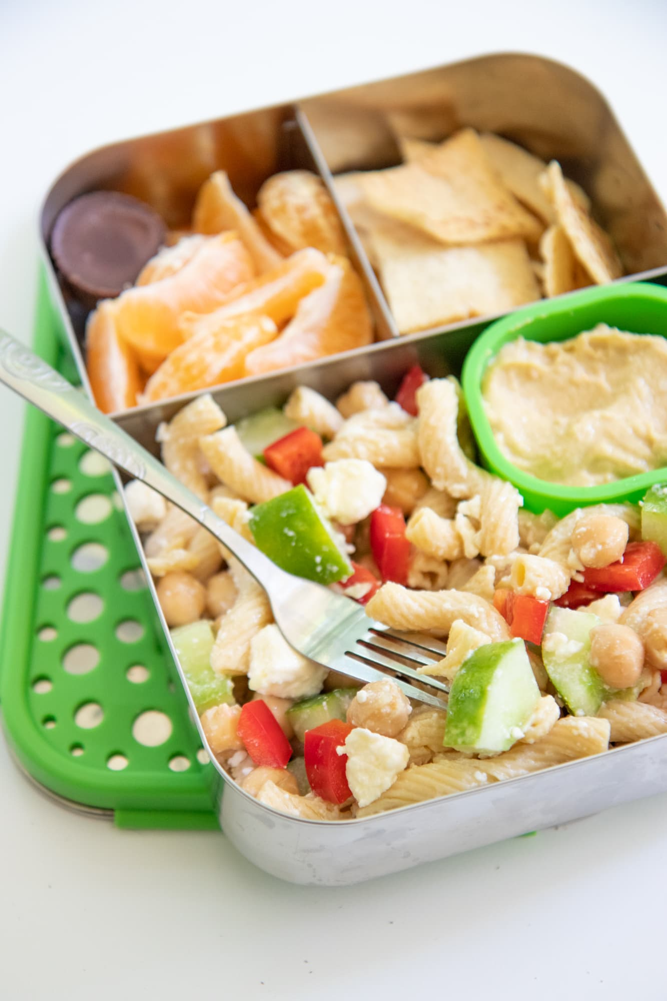 Stainless steel lunchbox with pasta salad, orange slices, and pita chips.