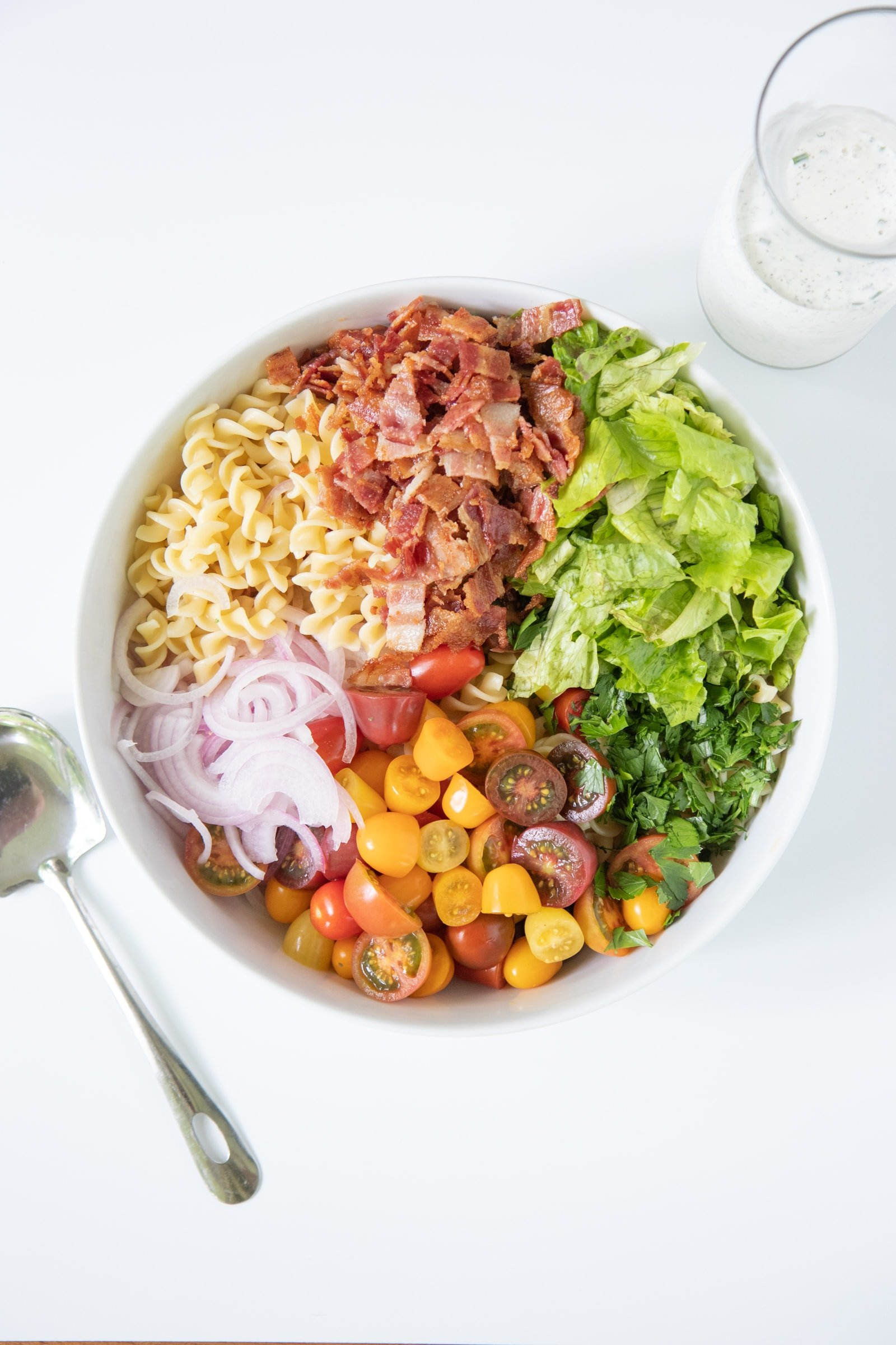 Ingredients for Ranch BLT Pasta Salad in a white bowl, before mixing