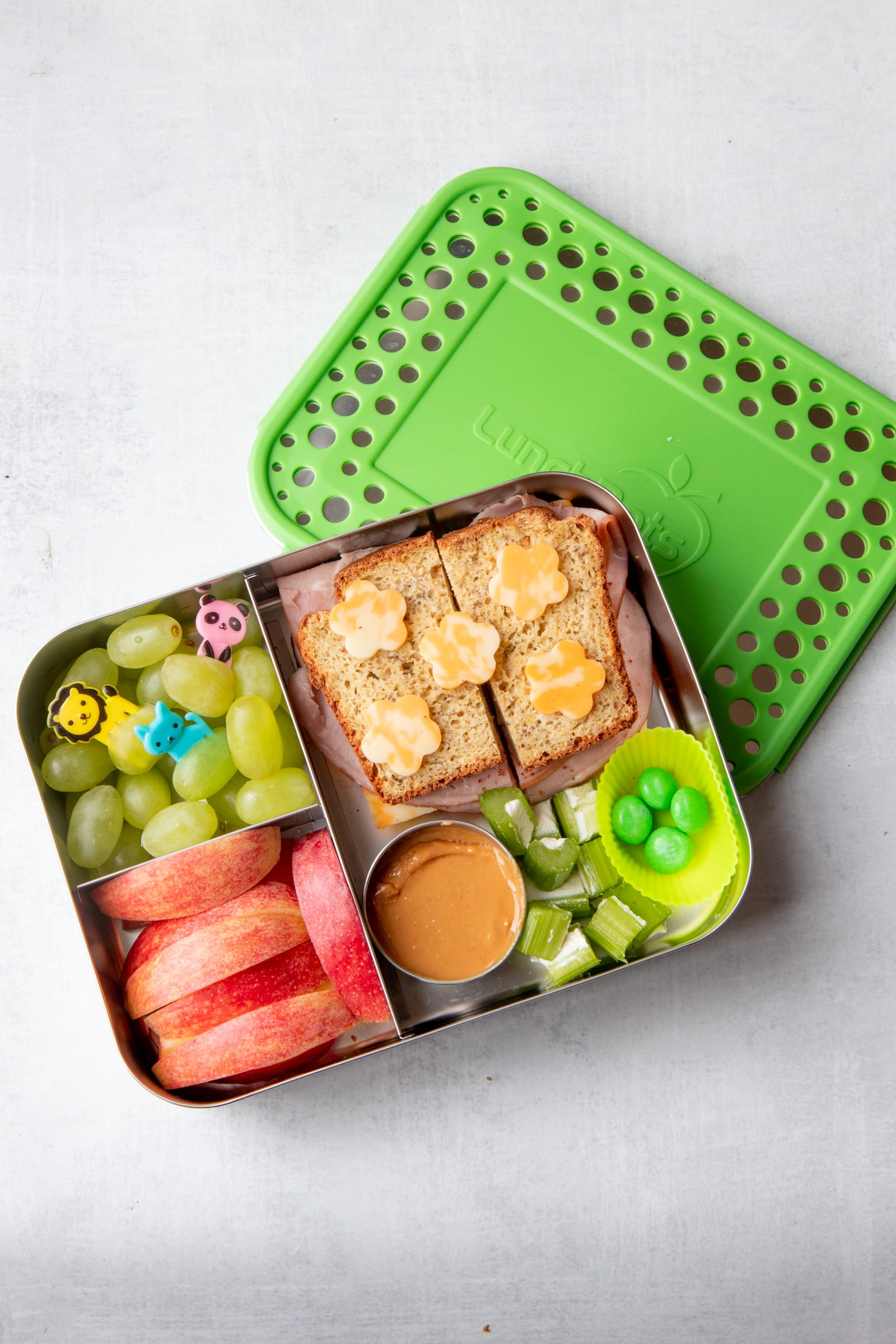 A zero-waste packed lunch consisting of a divided lunch box with a sandwich, grapes, apple slices, and celery.