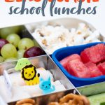 """Stainless steel bento-style lunchbox filled with a snack lunch: pretzels and dip, grapes, watermelon, popcorn, cucumber spears, and deli meat roll-ups. A text overlay reads """"How to Pack Zero Waste School Lunches."""""""