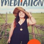 """Woman in a black dress and floppy hat standing outside and smiling. A text overlay reads """"Body Love Meditation. Free!"""""""