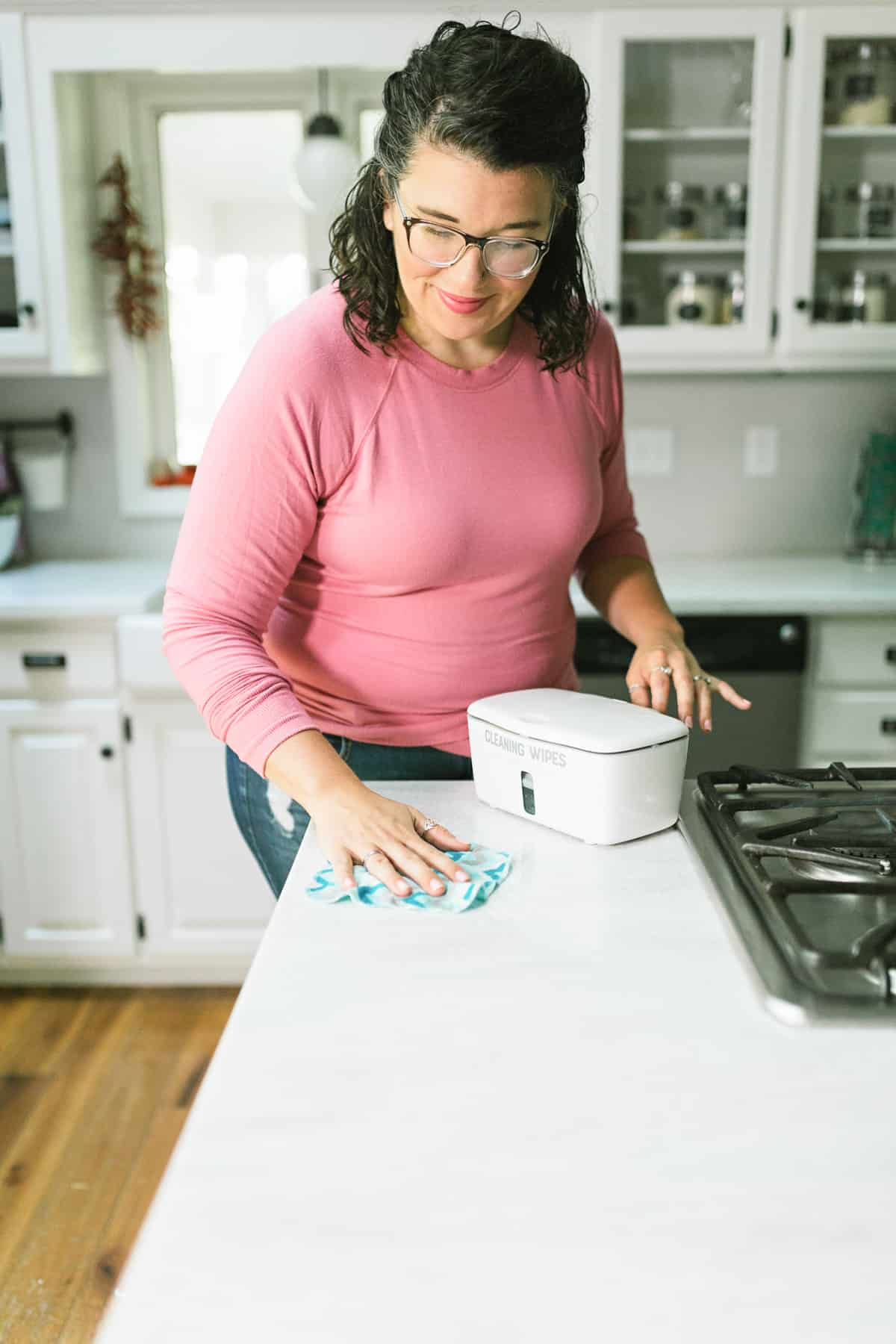 Woman using a DIY Disinfecting Wipe to clean a counter.
