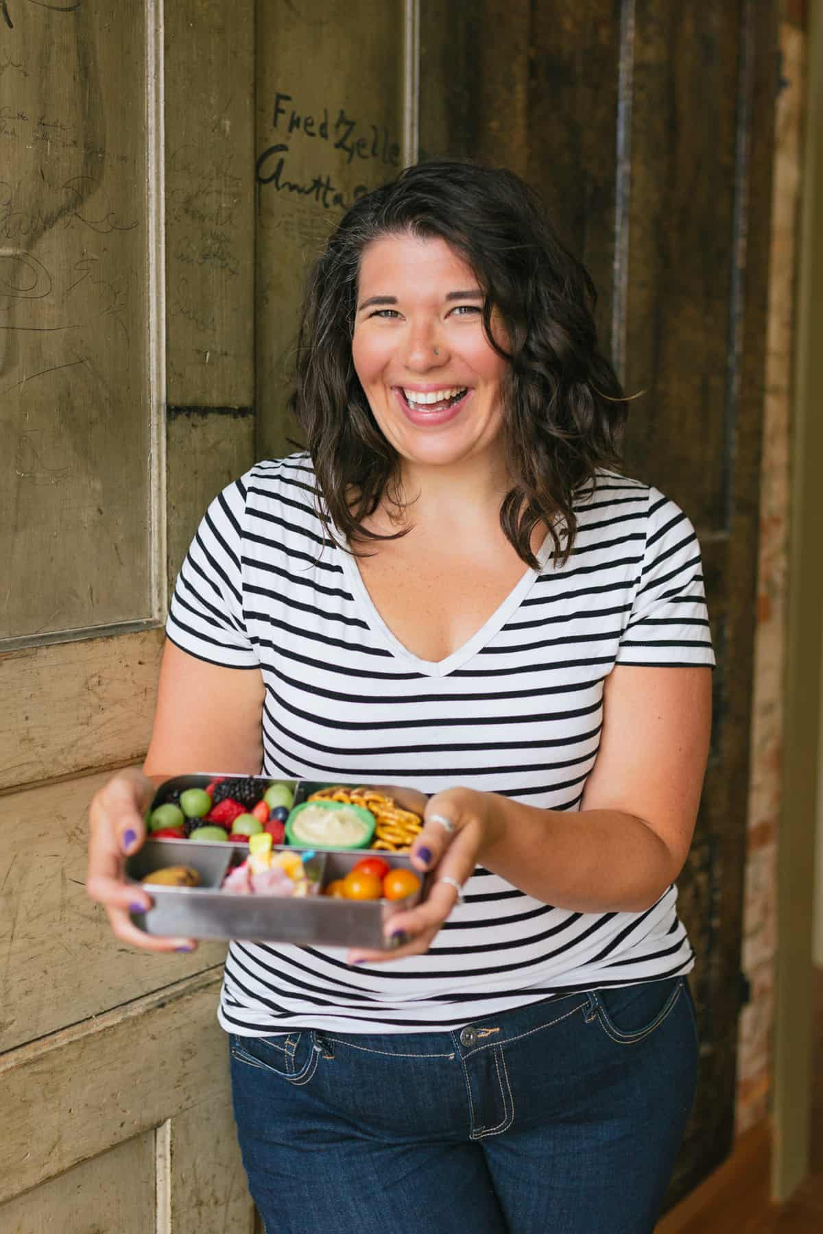 Brunette woman in a striped shirt holding a bento-style lunch box and smiling.