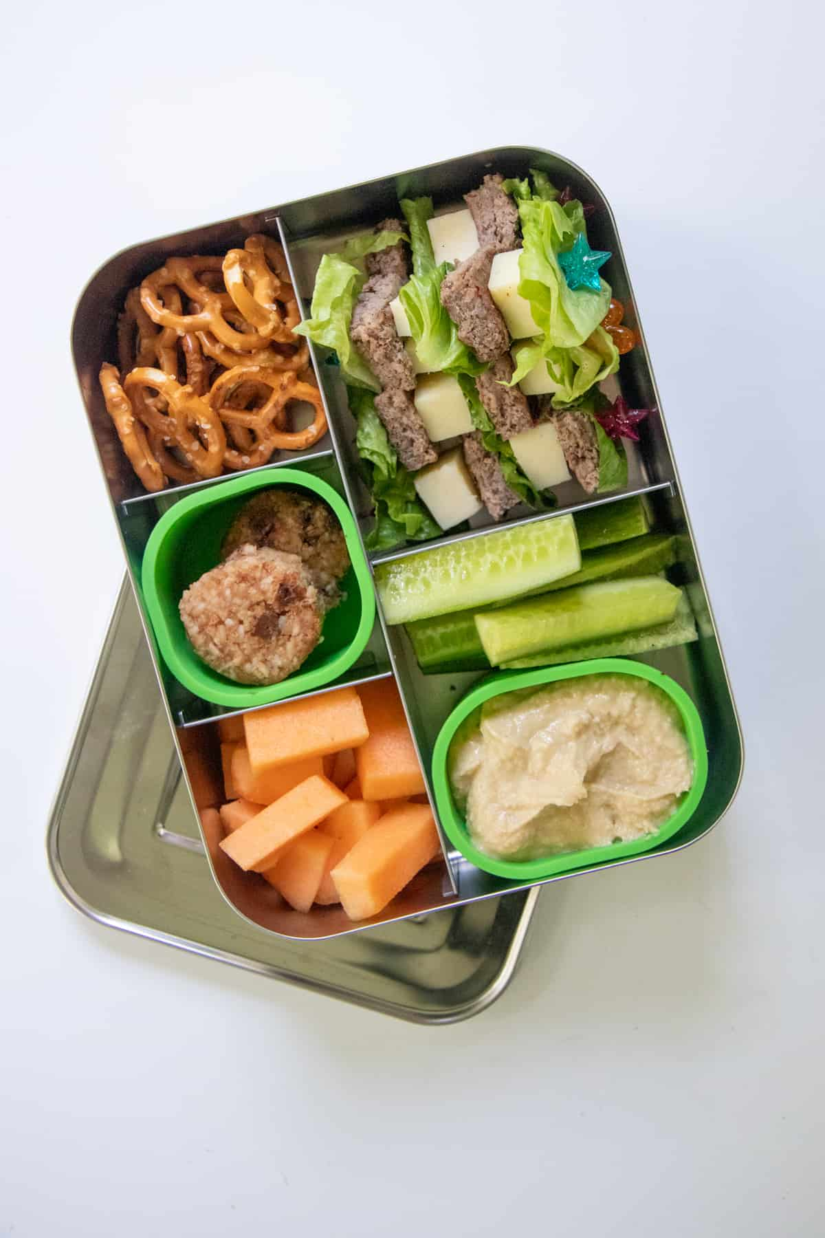 Stainless steel lunchbox filled with a school lunch idea: cheeseburger skewers with melon, pretzels, vegetables and hummus, and cookies