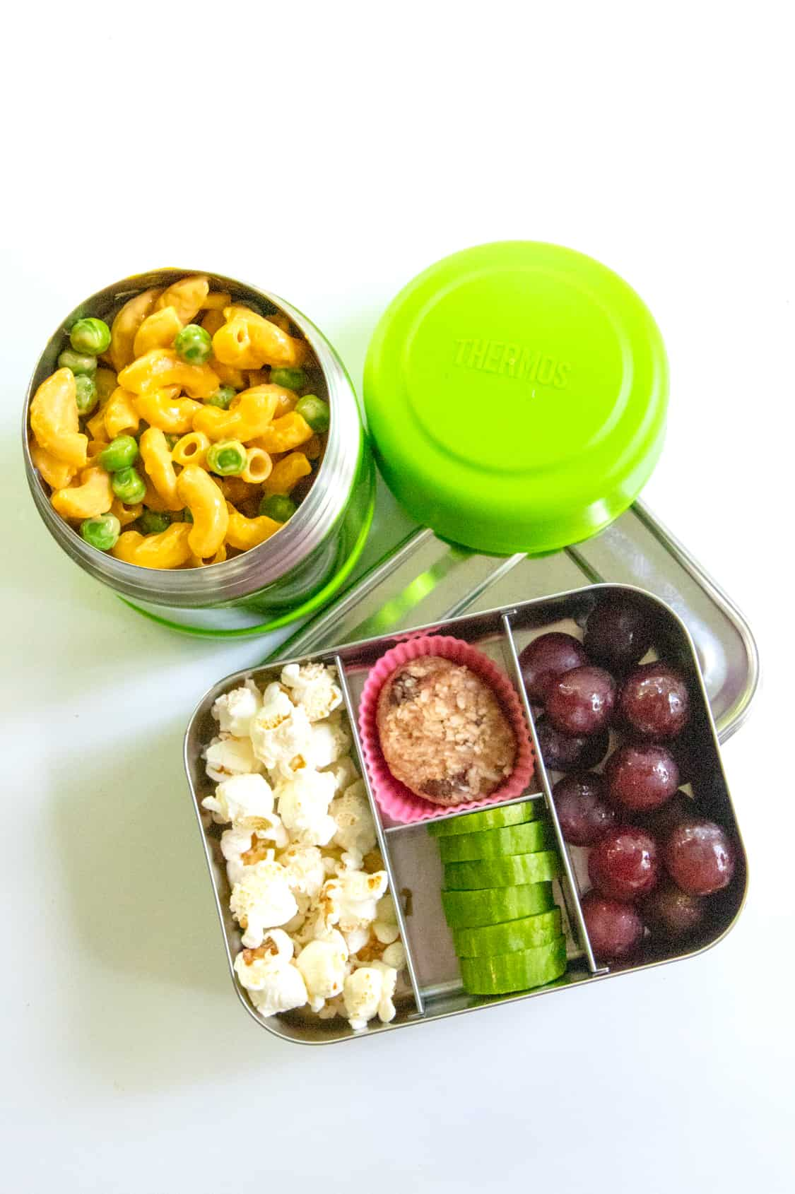 School lunch idea: Bento-style lunch box with popcorn, grapes, cucumber, and cookies next to a Thermos of mac and cheese.