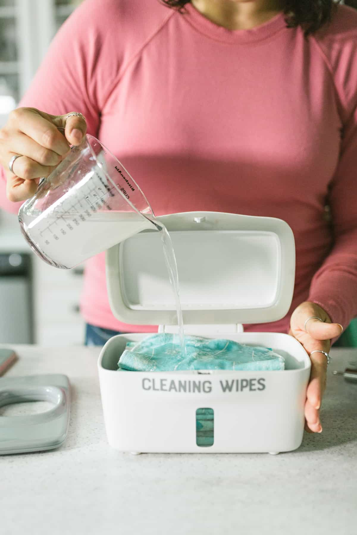 Woman's hands pouring a glass measuring cup of cleaning solution over a container of reusable wipes.