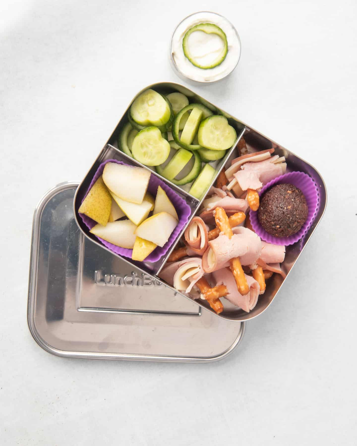 Another school lunch idea packed into a lunch box: ham and cheese roll-ups on pretzel stick skewers, fruit, and cucumbers.
