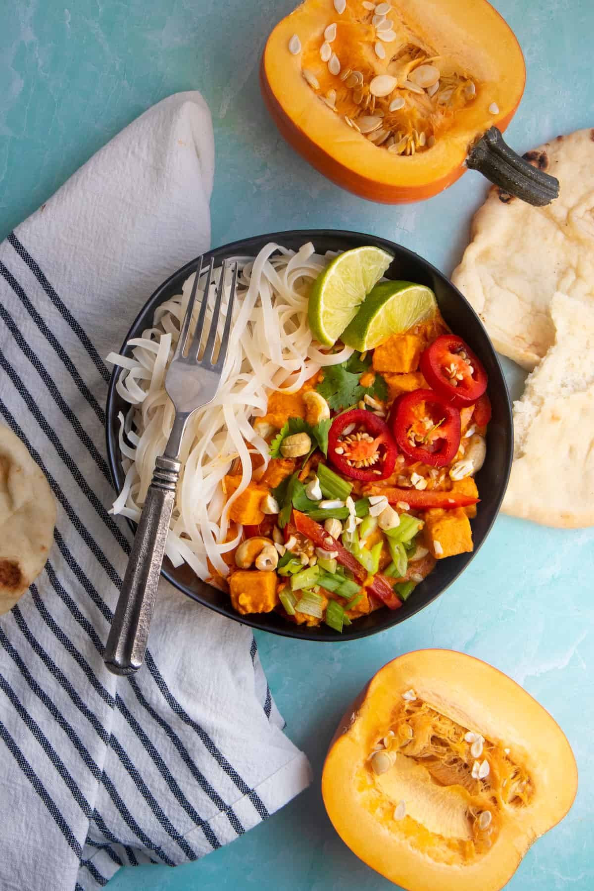 Black dish of one pot pumpkin curry and rice noodles next to a halved pumpkin.