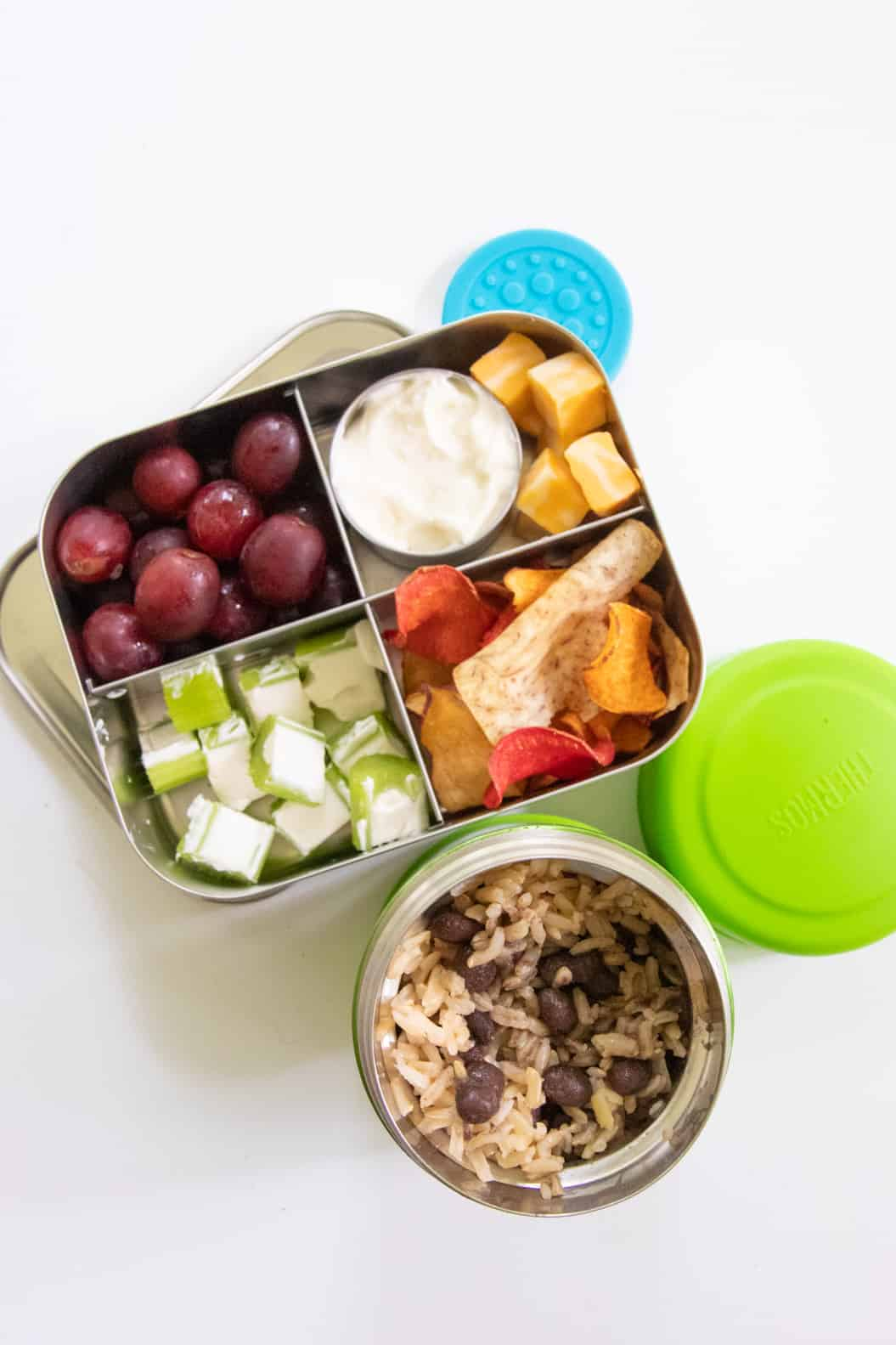 Stainless steel lunch box with grapes, cheese, ants on a log, and veggie chips, next to a Thermos of rice and beans