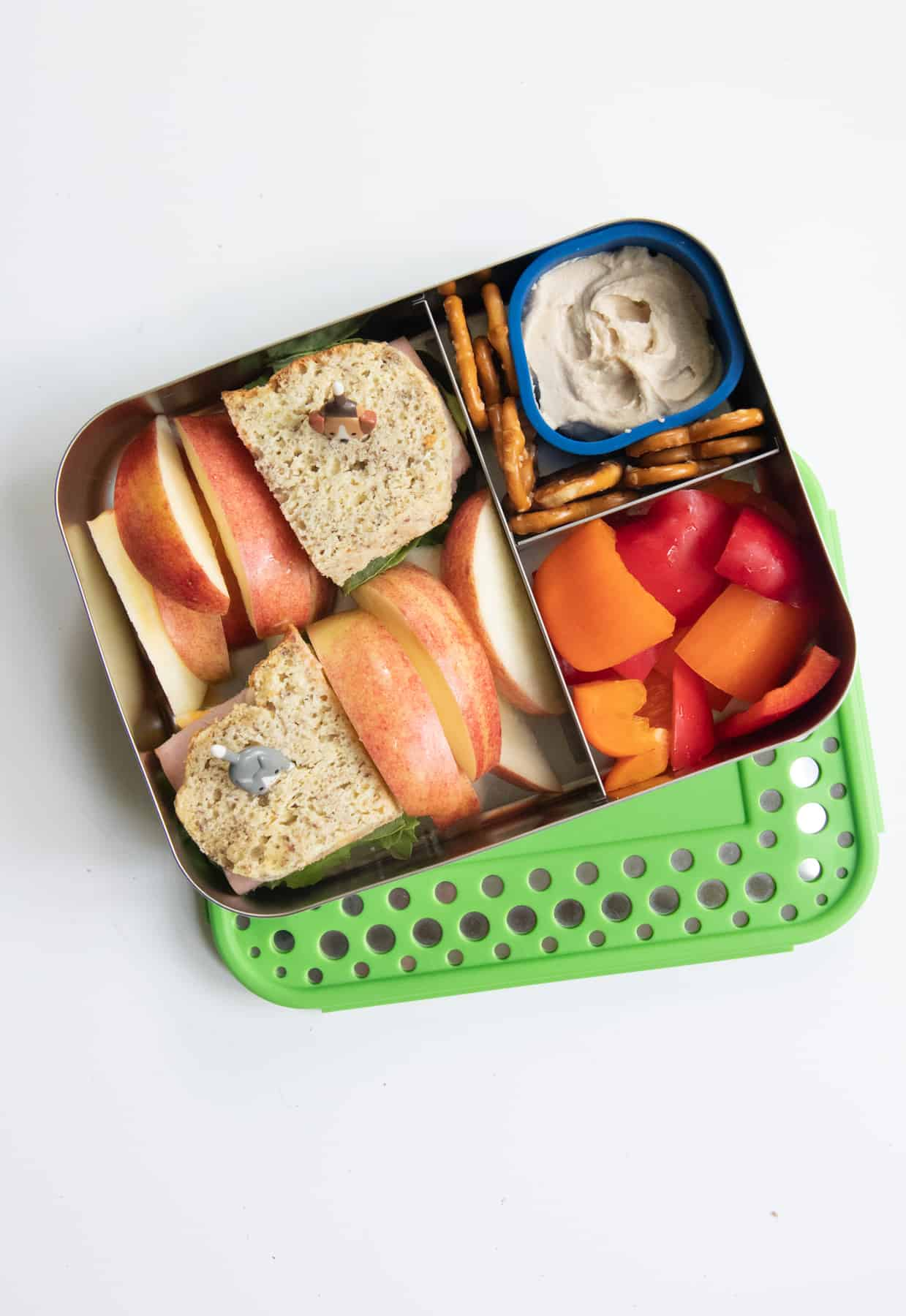 Stainless steel lunch box with a sandwich, apple slices, peppers, and pretzels with hummus.