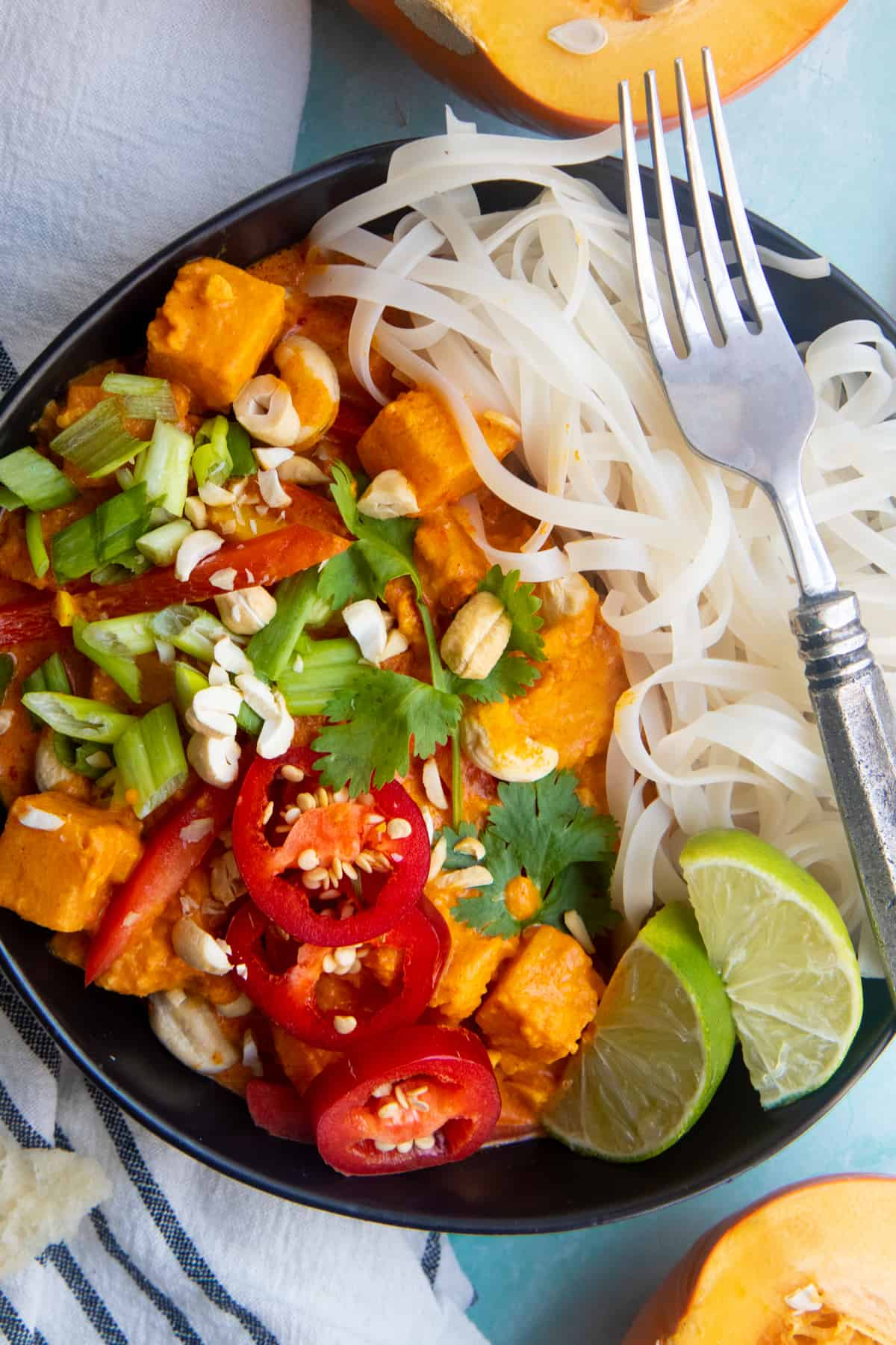 Overhead shot of one pot pumpkin curry served over a bed of rice noodles, in a black dish on a light blue table.