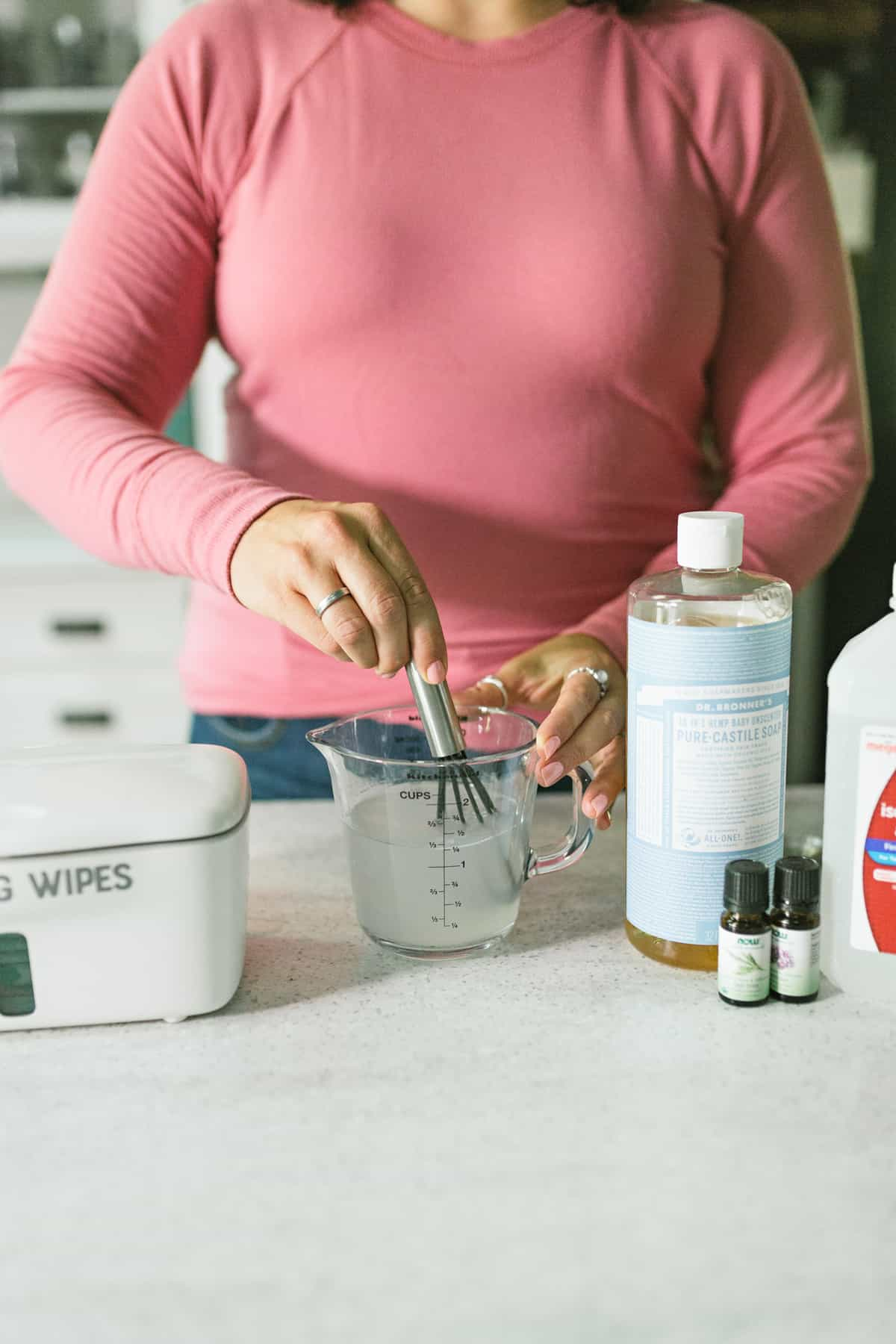 Woman in a pink shirt whisking together a cleaning solution for DIY Disinfecting Wipes