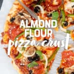 """Baked veggie pizza sliced and sitting on parchment paper. A text overlay reads """"Almond Flour Pizza Crust."""""""