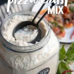 """A measuring cup dips into a large open jar of almond flour pizza crust mix. A text overlay reads """"Paleo Pizza Crust Mix."""""""