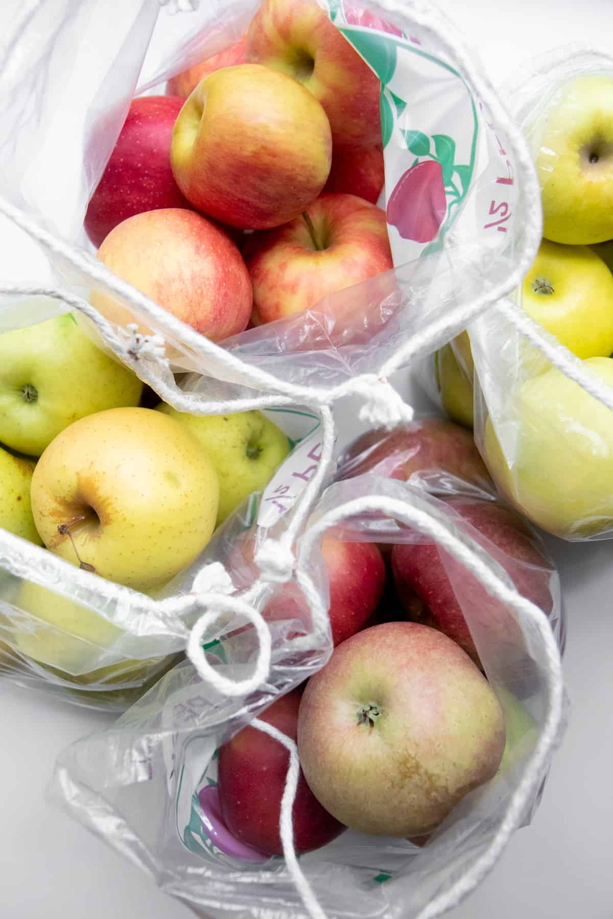 Clear plastic drawstring bags full of apples.