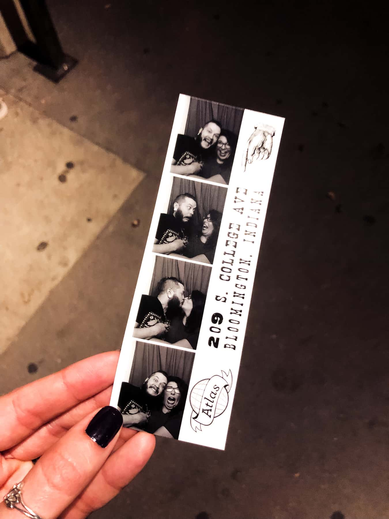 A woman's hand holds a strip of pictures from a photo booth.
