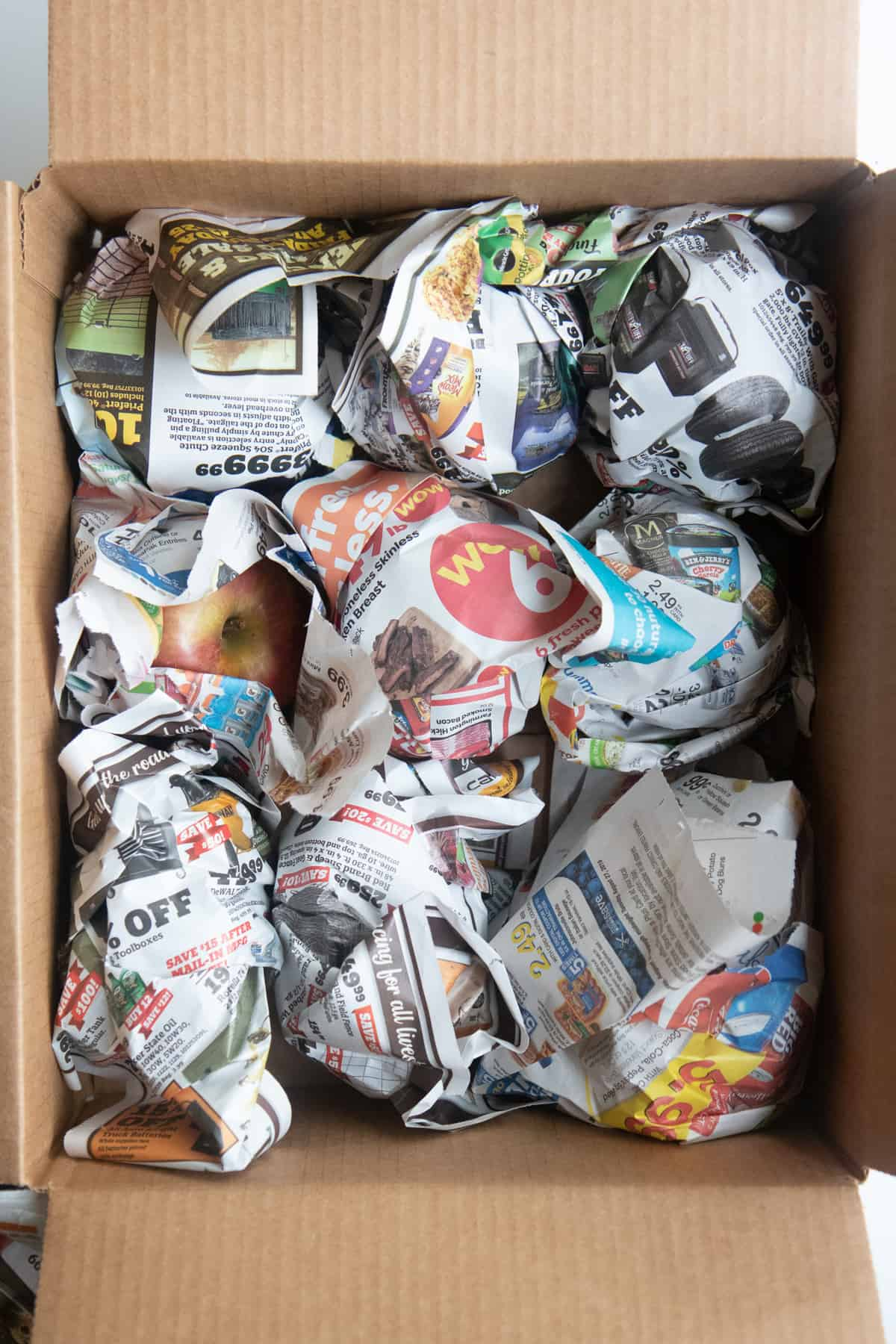 Bunches of newspaper wrapped around apples line a box.