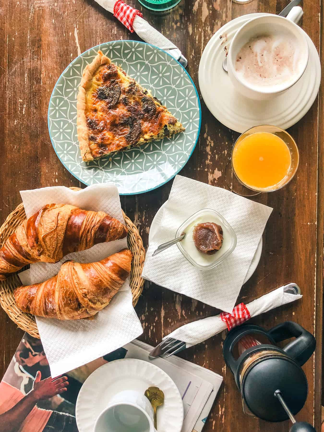 Breakfast consisting of yogurt with chestnut cream, croissants, quiche, juice, and coffee is laid out on a wooden table.