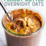 """Close up of peanut butter chocolate overnight oats in a glass jar. There are peanuts garnishing the top, and a spoon dips into the jar. A text overlay reads """"Chocolate Peanut Butter Overnight Oats."""""""