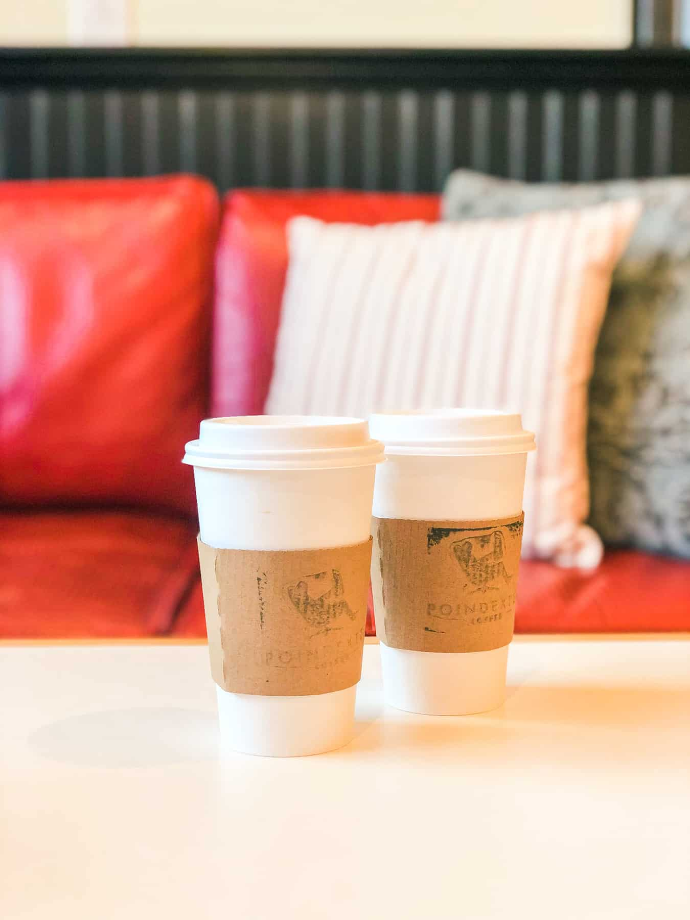 Two paper to-go coffee cups with cardboard sleeves sit on a table in front of a red couch.