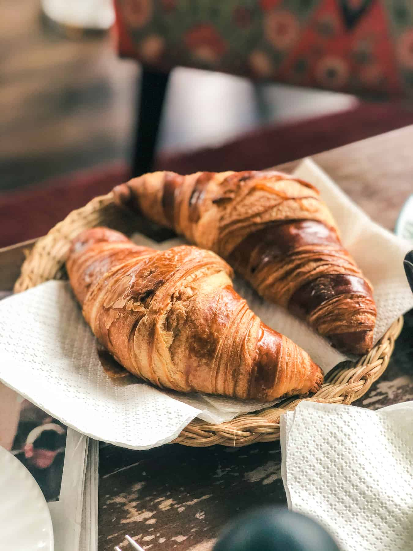 Two croissants sit on a white napkin in a woven basket.