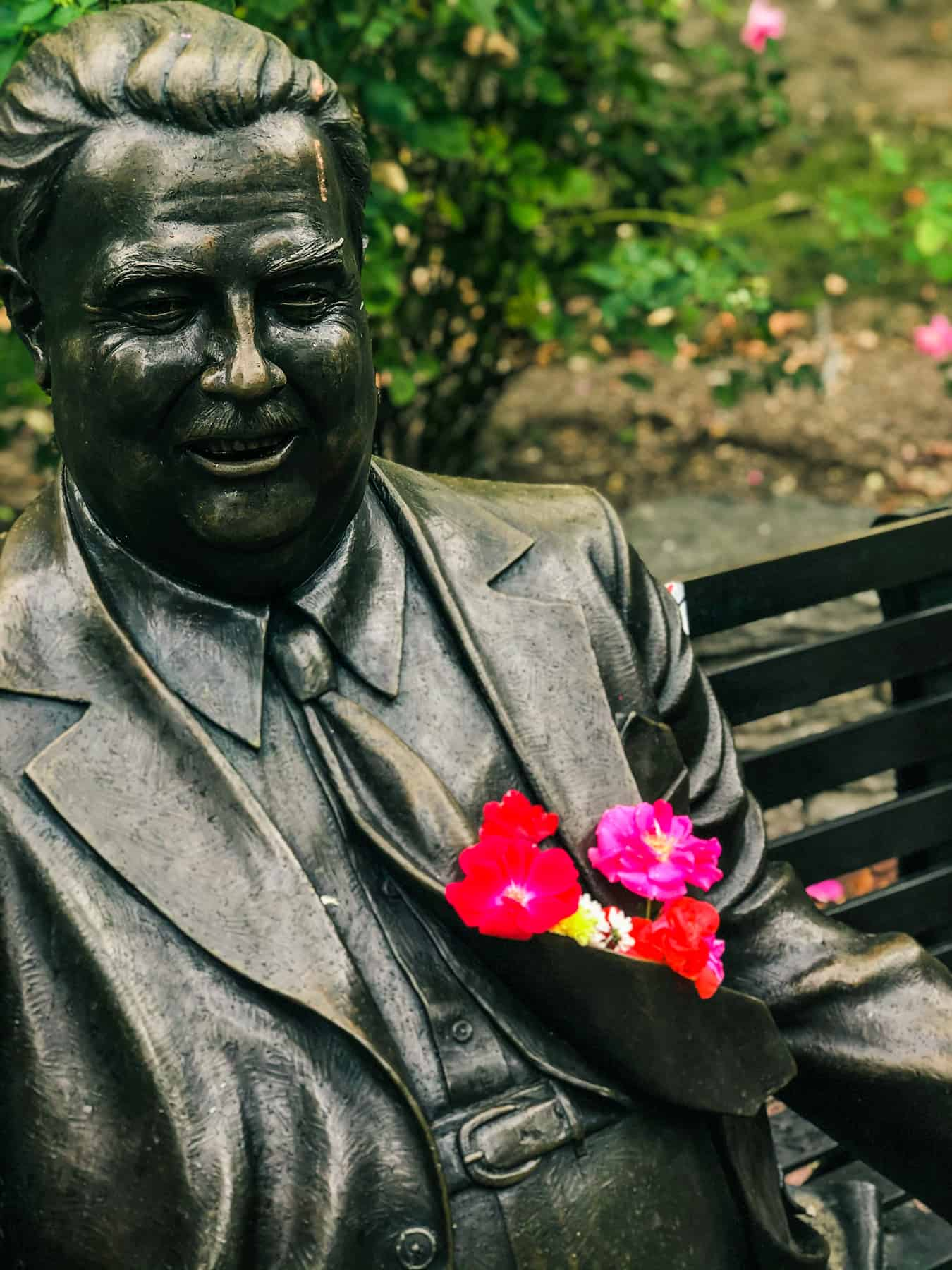 Statue of Herman Wells in Bloomington, IN, with flowers tucked into the coat pocket.
