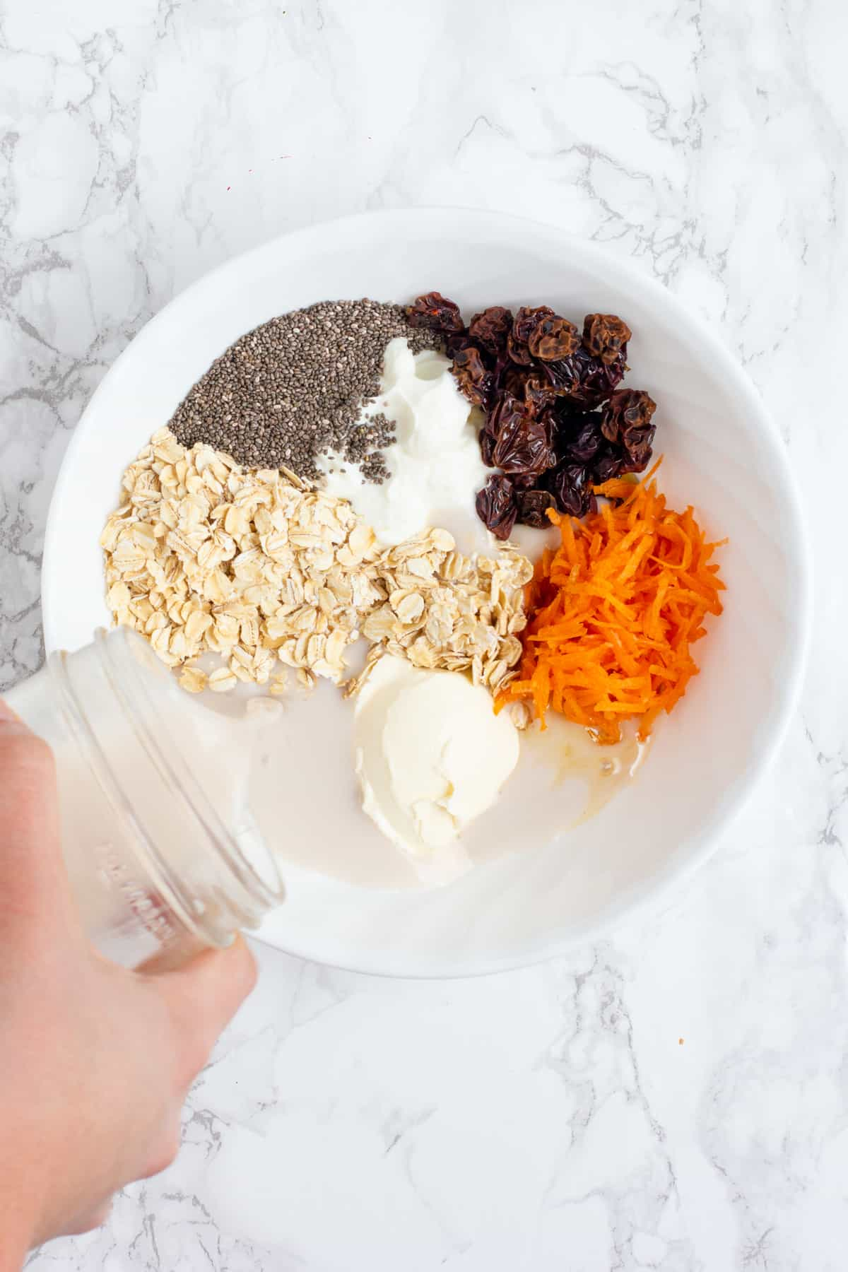 A hand pours milk from a glass jar into a white bowl. The white bowl is filled with other ingredients, including cream cheese, yogurt, shredded carrots, raisins, chia seeds, and rolled oats.