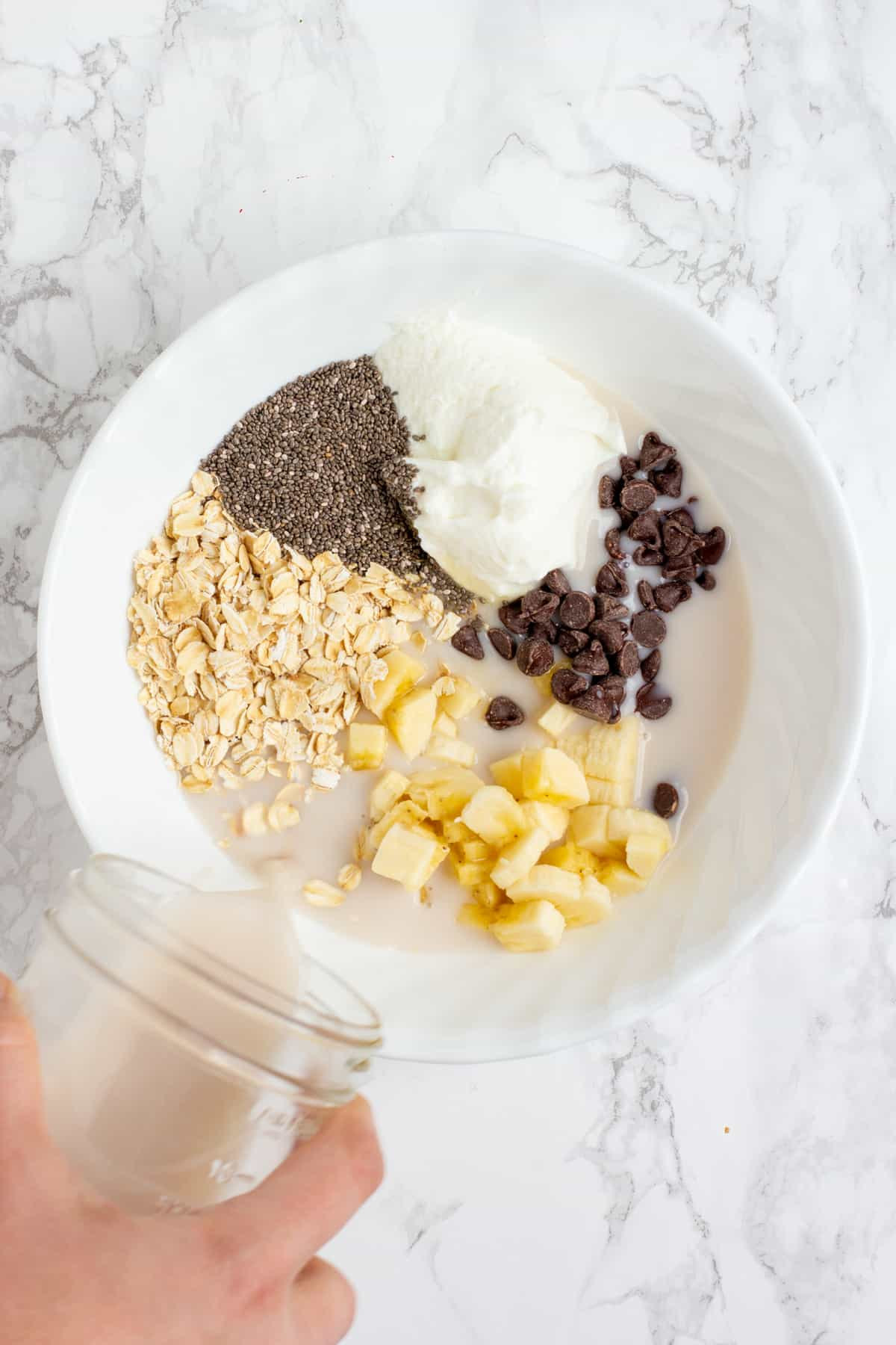 A hand pours milk from a glass jar into a white bowl. The white bowl is filled with other ingredients, including yogurt, chopped banana, chocolate chips, chia seeds, and rolled oats.