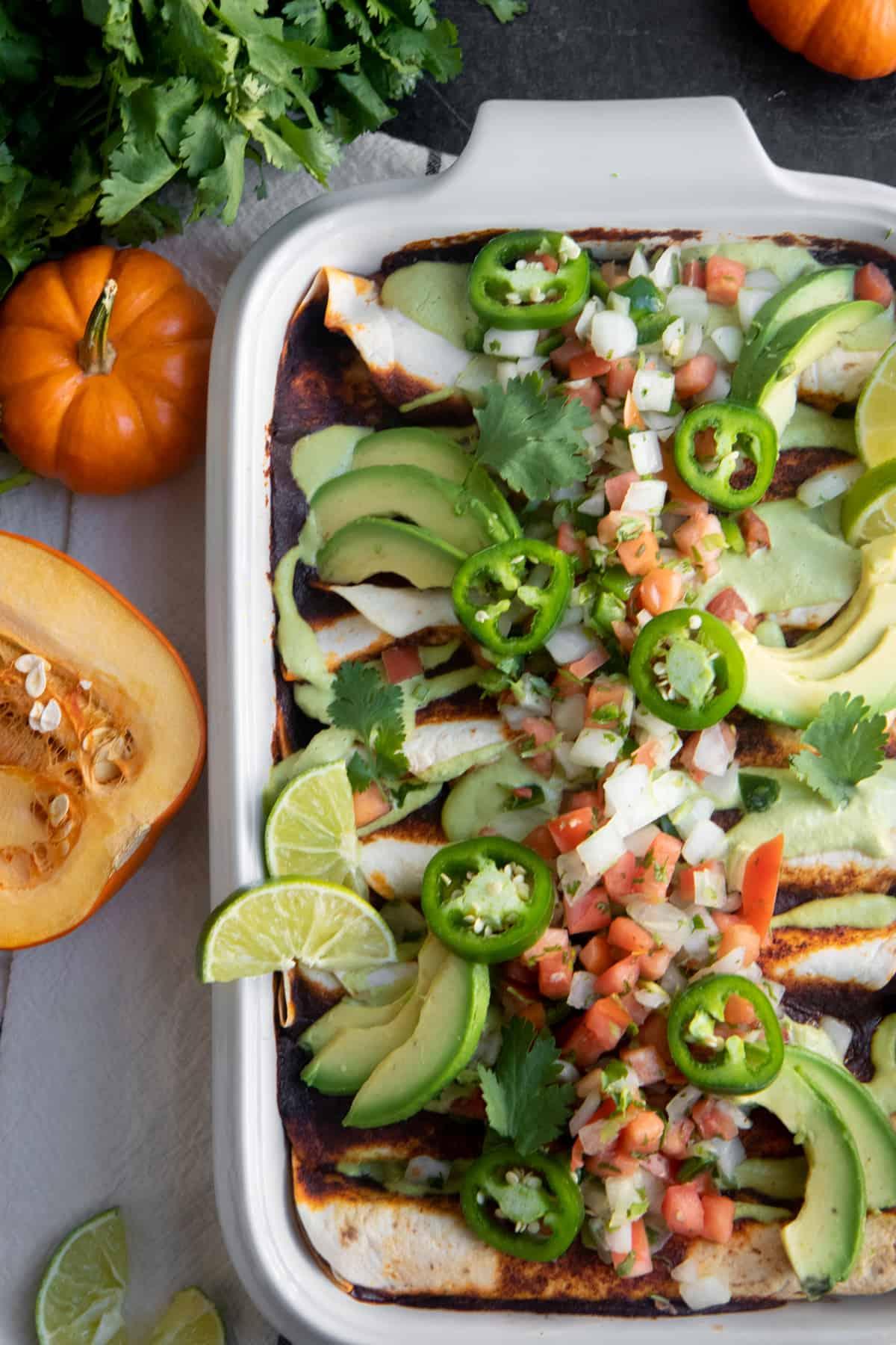 Close up of vegan enchiladas, topped with lime, avocado, and jalapeno.