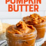 """Two glass jars filled with Slow Cooker Pumpkin Butter, next to biscuits and a plate. A text overlay reads """"Slow Cooker Pumpkin Butter."""""""