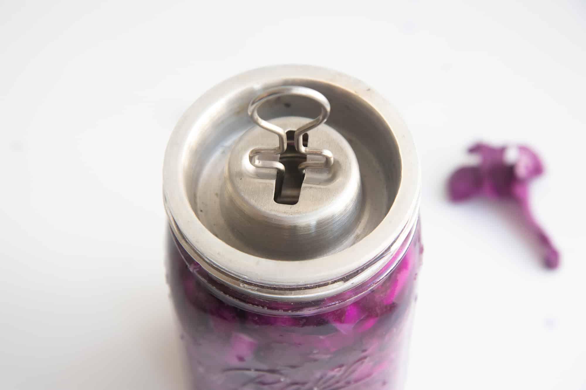 A fermentation lid sits on top of a glass jar of homemade sauerkraut.