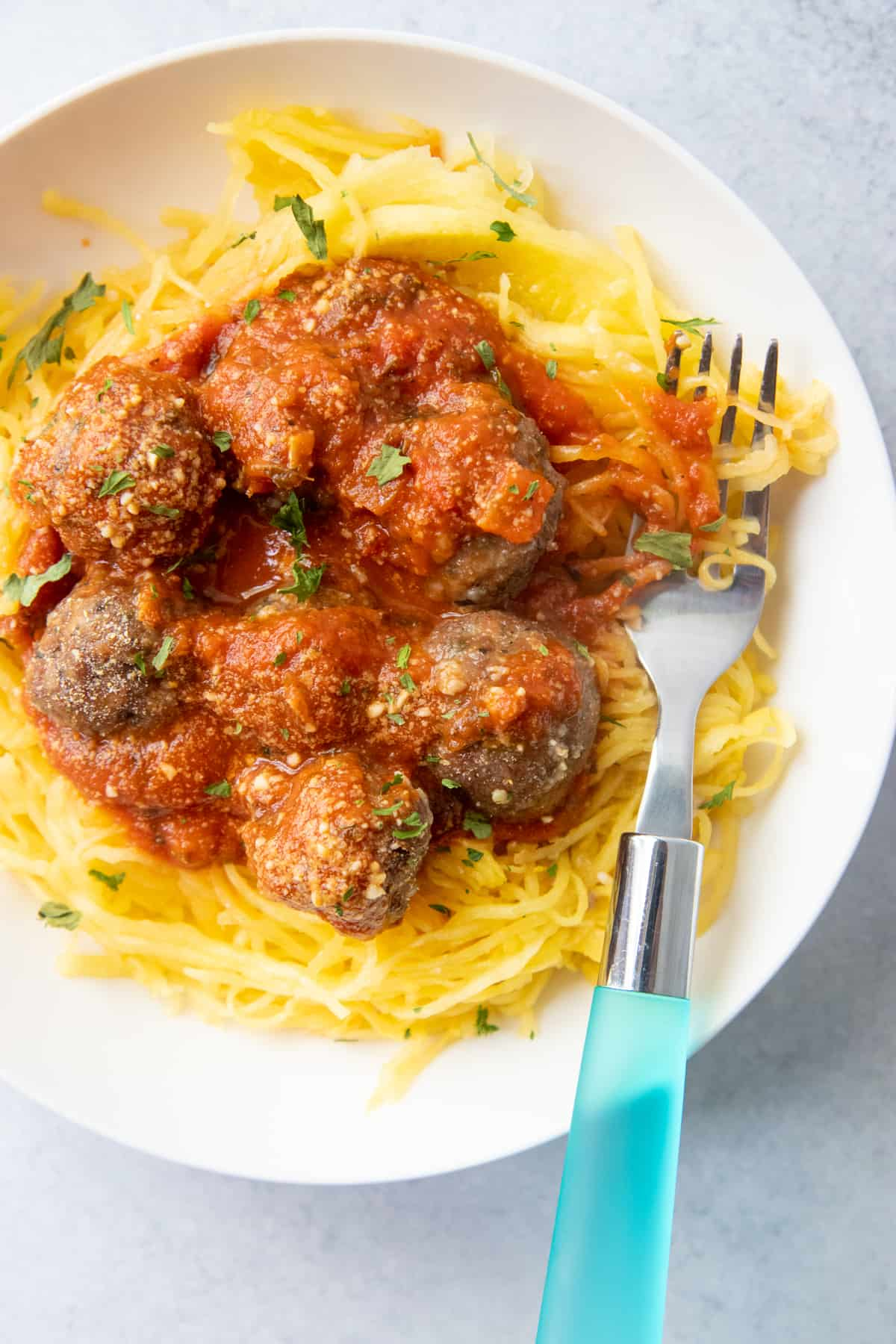 Spaghetti squash noodles are covered in marinara and topped with meatballs. The noodles are on a white plate with a blue-handled fork.