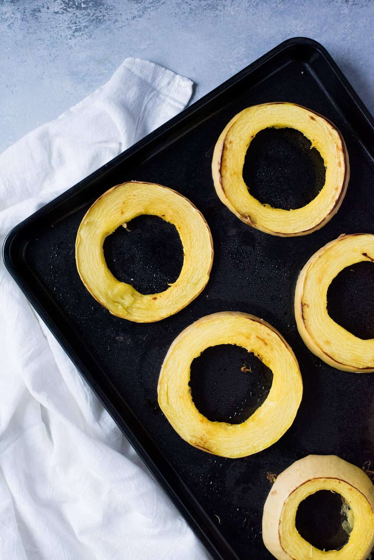 Rings of spaghetti squash spread out on a baking sheet.