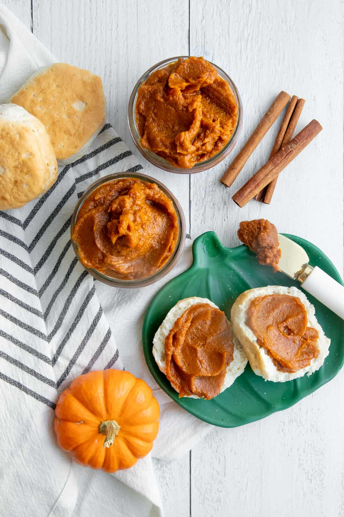 Pumpkin butter spread on a split biscuit, which is sitting on a pumpkin-shaped plate.