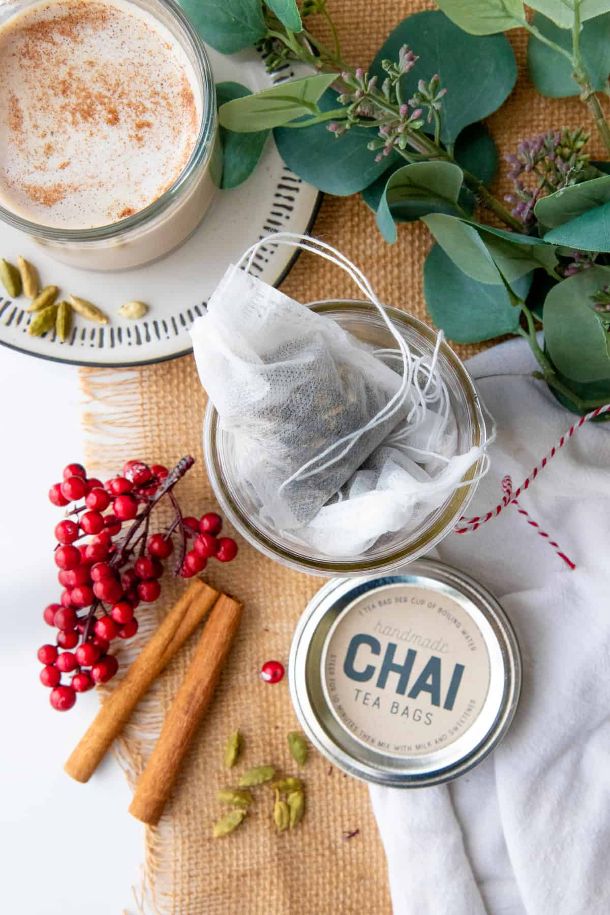 Tea bags filled with chai mix are in a glass mason jar surrounded by spices.