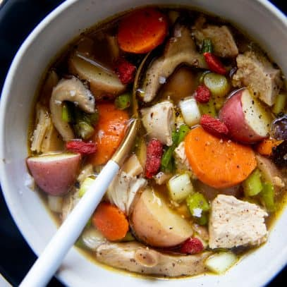 A spoon with a white handle sits in a white bowl full of Instant Pot herbal chicken soup.