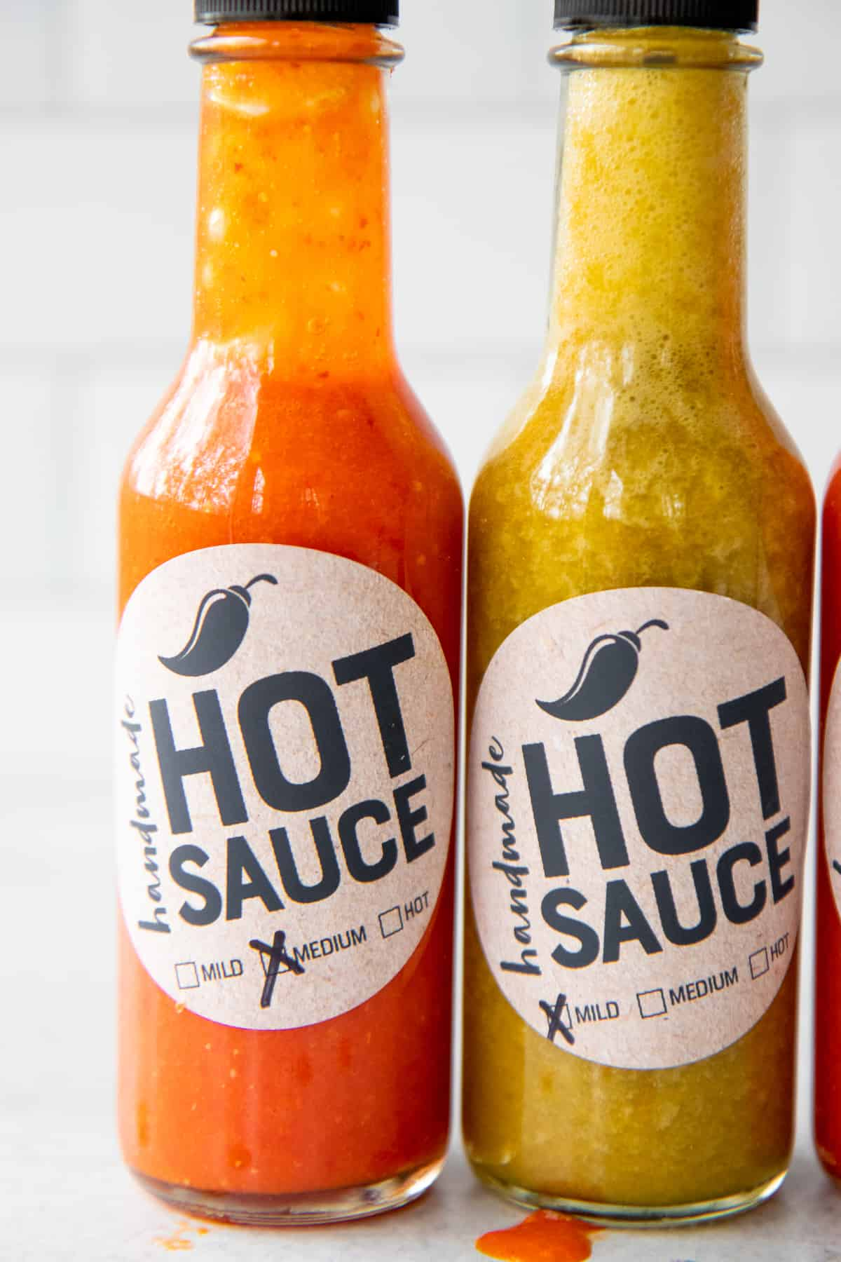 Two bottles of homemade hot sauce, with printable labels.