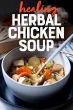 """A spoon with a white handle sits in a white bowl full of herbal chicken soup. A text overlay reads """"Healing Herbal Chicken Soup."""""""