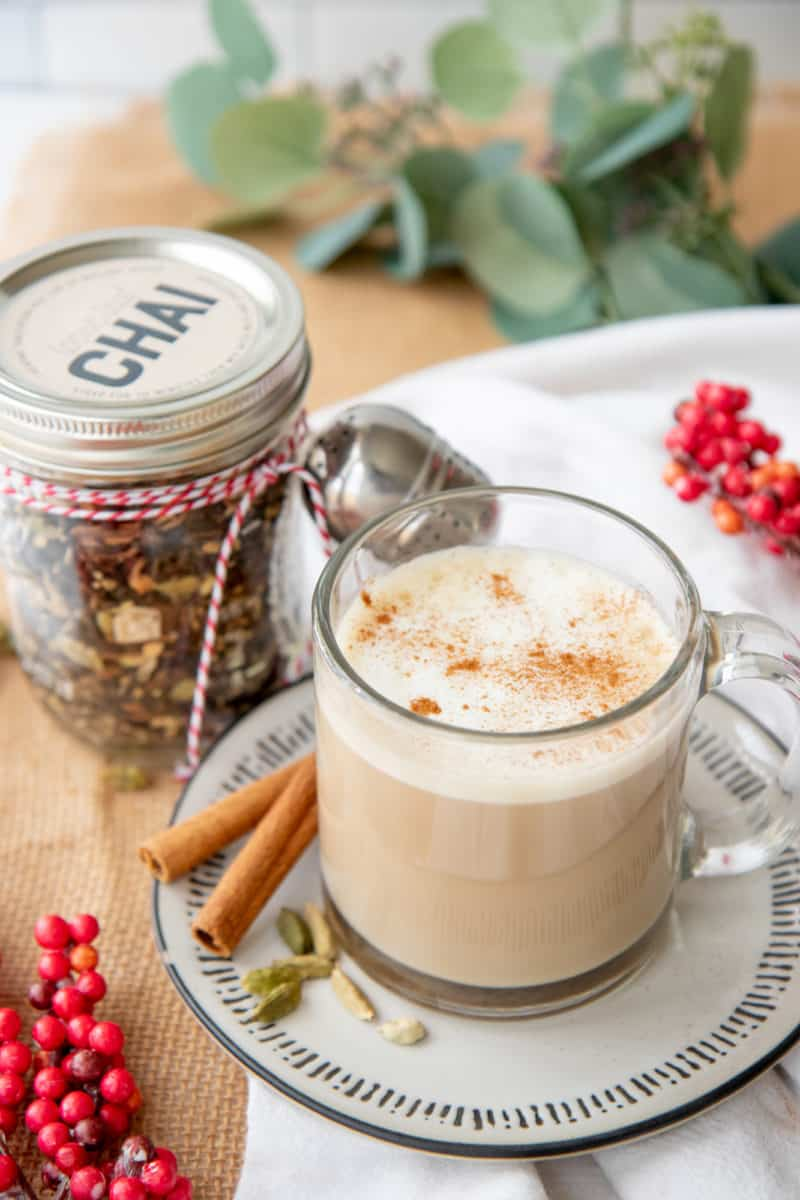 A glass mug filled with a chai latte sits in front of a jar of loose leaf chai mix.