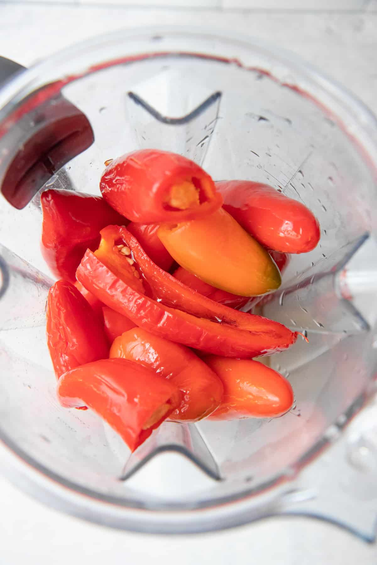 Fermented red peppers in the basin of a blender.